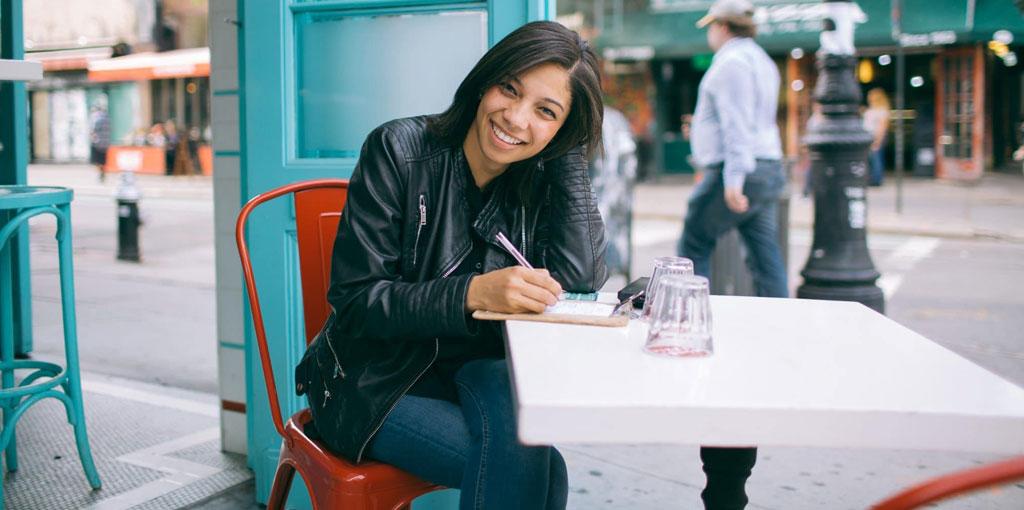 Woman writing at a café